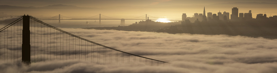 sun rising over San Francisco skyline, fog under the Golden Gate Bridge