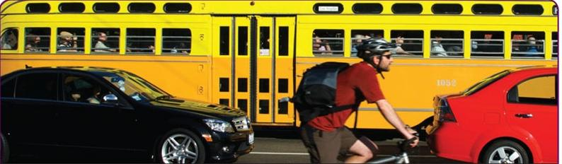 Man riding bicycle with black car, red car, and muni train in the background