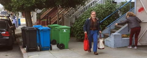resident with bags and walking next to three bins