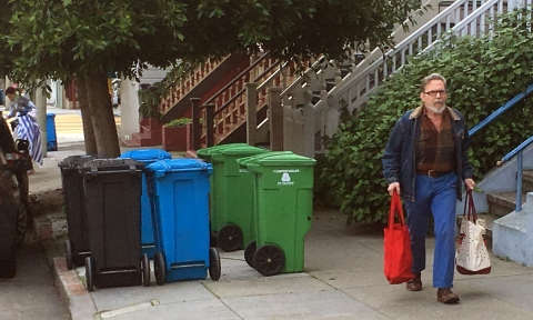 residents in english link, photo of man with bags and three bins