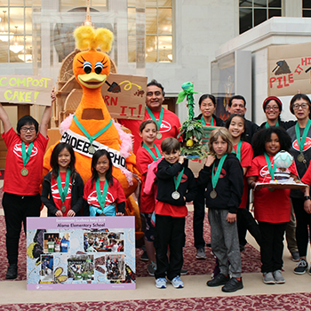Group of students celebrates their environmental award medals with our mascot, Phoebe the Phoenix.