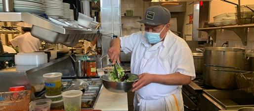 Man with mask preparing food in restaurant kitchen